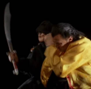 Steven Seagal lashing out at a lunging ninja, arms and swords flailing
